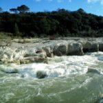 Die beiden unteren Drittel des Bildes zeigen Kaskaden und Felsen in Grau und weiß mit wildem Wasser. Im Hintergrund teilen sich dunkelgrüne Pinien und blauer Himmel das obere Drittel.