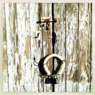 Ein rostiger Riegel über einem mit Riffelkunststoff ummantelten Draht in O-Form, an dem ein schwarzes Vorhängeschloss hängt schließt hölzerne Torflügel mi abblätternder Kalkfarbe.