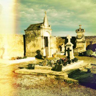 Ein Fehlfarbenstreifen wie von Lichtverblitztem altem Farbfilm links begleitet das Auge auf einen französischen Friedhof. Im Zentrum eine große Gruft vor Friedhofsmauer und ein kleineres Grab mit vielen Sogenannten Souvenirs.