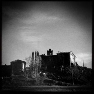 Schwarz-Weiß-Bild einer katalanischen Kirche ein bisschen Underfoot aufgenommen im Gegenlicht. Dunkle Vignette an den oberen Bildecken. Kahle Bäume geleiten den Blick.