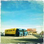 Autobahnrastplatz in Siebziger hellblau-gelb-Fehlfarben. Zwei LKW nebeneinander vor einem Hotel. Betonblockaden führen den Betrachter zum Hoteleingang. Der blaue Himmel nimmt fast drei Viertel der Bildfläche ein.