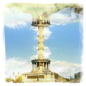 Die Berliner Siegssäule gespieglt und in ihren eigenen Kopf kopiert, so dass ein Streifen Himmel mit Schönwetterwolken zwischen den oben und unten liegenden Säulengebäudem am Sockel der Säule liegt wie die Spiegelung in einem See.