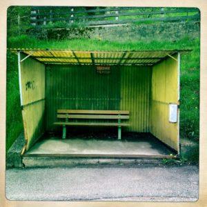 Giftgrüne Aufnahme einer mit gewelltem Polyester umgebenen Bushaltestelle, in der eine Parkbank steht. Mittig im Fon des Häusens ein rotes Schild, auf dem man den Schriftzug Defense erkennt.