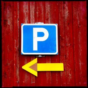 Parkplatzschild über gelbem, nach links zeigendem Pfeil an roter Holzbretterwand.