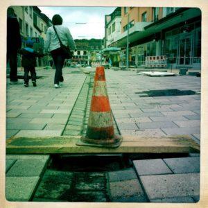 Underfoot-Aufnahme einer nicht fertig gestellten Pflasterung in einer Fußgängerzone. Rot-weißer Pylon auf Brett über dem Loch eines Kanals. Daneben zwei Erwachsene mit mittig an den Händen geführtem Kind.