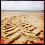 Riesige, Fischrätenartige Traktorreifenspur im Sand vor grauem Meer.