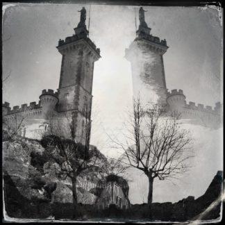Schwarz-weiß-Retro-Bild eines quadratischen Turms, auf dem eine Skulptur steht. Zwischen den beiden Spiegelungen strahlt ein heller Schimmer.