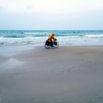 Schwer bepackter Reiseradler mit gelber Regejacke vor verregnetem Meer auf Sandstrand radelt von links nach rechts.
