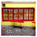 Gelbe Fassade mit knallroten Rasterfenstern, darauf die Zahlen 0816 und davor knallrote Terrassentische auf Kopfsteinpflaster.