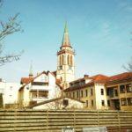 Hinter einem längs vernagelten Bretterzaun lugt eine Dorfkulisse nebst Kirchturm hervor.