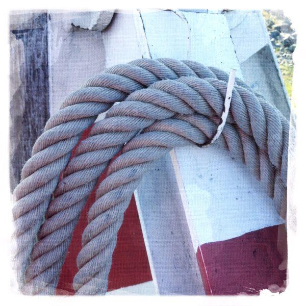 Ein Detail eines Rettungsrings, auf dem ein dickes Tau gewunden ist.