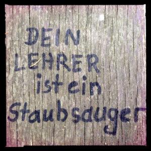 Mit Edding geschrieben auf Holzbank: Dein Lehrer ist ein Staubsauger. Schwarz umrandet.