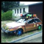 Ein braunes, reichlich mit buntem dekoriertes altes Auto steht Bildfüllend vor einem Wohnhaus.