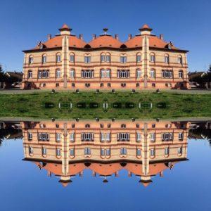 Zackiges Backsteinhaus, mehrfach gespiegelt und wie in einem Kaleidsokop zusammengesetzt. Es wirkt wie eine Spiegelung im Wasser.