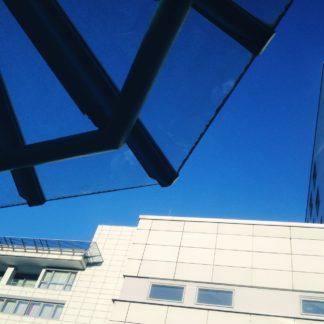 Wie ein nlandendes UFO schiebt sich die gläsern-stählerne Konstruktion des Dachs eines Pavillons in den blauen Himmel. Im hintergrund die leicht überbelichtete Fassade eines mehrstöckigen Krankenhausgebäudes.