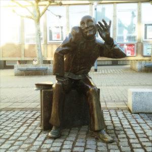 Eine sitzende Bronzefigur, lebensgroß auf innerstädtischem Platz, hält die linke Hand lauschend ans Ohr und reckt markant den Kopf.