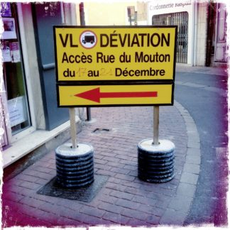 Französische Sprache auf einem großen, gelben, rechteckigen Umleitungsschild auf einem innerstädtischen Gehweg, der durch das Schild fast vollständige verstellt wird.