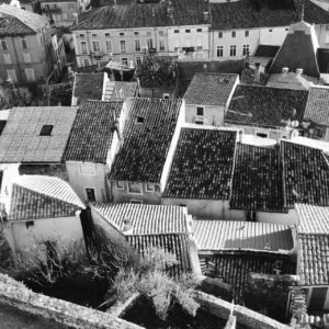 Von einer Burgmauer schaut man auf die Dächer einer dicht bebauten, verwinkelten Stadt. Schwarz-weiß-Aufnahme.
