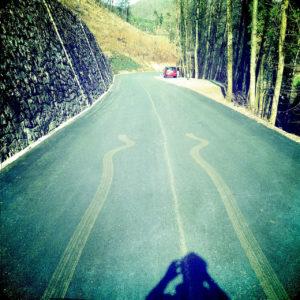 Eine schlingernde Dreckspur mitten auf der Straße endet abrupt in der Bildmitte. Im Hintergrund ein rotes Auto am bewaldeten Straßenrand. Rechts eine steile Stützmauer und vorne im Bild der Schatten des Fotografen.