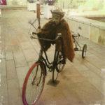 Auf einem alten Fahrrad sitzt ein pelziges Wesen mit Steampunk- Kopf und Gasmaske und viel alter Technik. Das Fahrrad hat einen Anhänger. Innenstädtisches, französisches Flair.