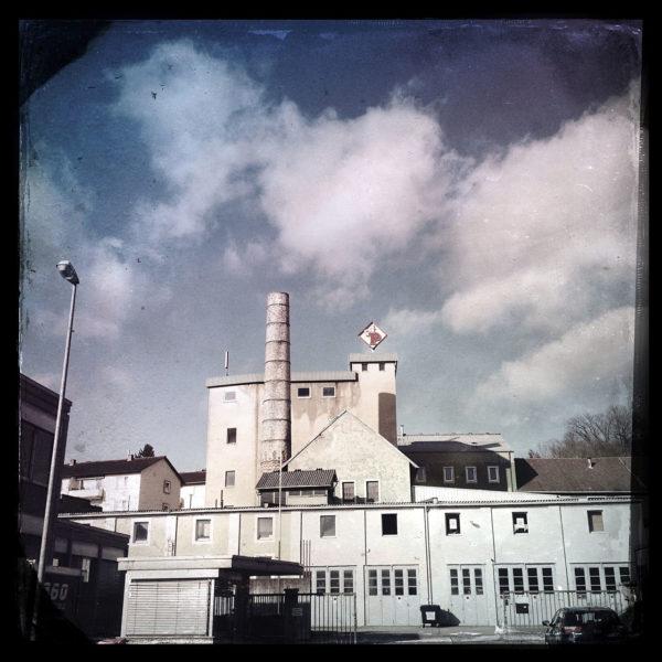 Retrofoto mit unsauberem, vignettierten Rand und bläulich scharz schimmernder Silhouette eines Fabrikgeländes. Ein markanter, runder Schlot ragt aus Backstein- und Betonbauwerken.