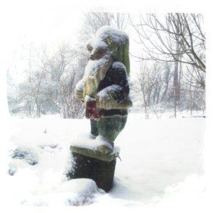 Im Schneetreiben steht zum Umfallen schräg ein Disney-Gartenzwerg auf einem kleinen Sockel. Tiefer Schnee vor Baumreihe.