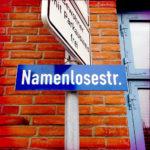 Straßenschild, blau, mit weißer Schrift, Deutschland, vor sattroter Backsteinmauer. Namenlosestr.
