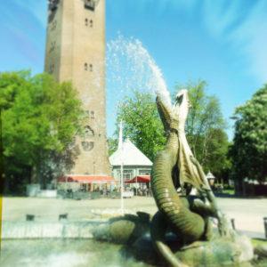 Eine sich aufbäumende Drachenfigur in einem Brunnen speiht Wasser. Im Hintergrund des sommerlichen städtischen Platzes steht ein quadratischer Backsteinturm.