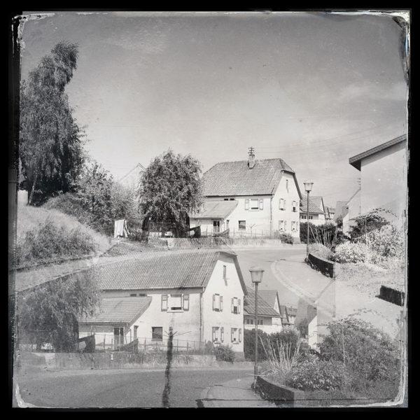Bildüberblendung schwarz-weiß eines Hauses mit Krüppelwalmdach