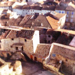 Blick auf die Dächer eines alten französischen Städtchens mit viel Ziegel, Winkeln und Aneinanderbauten.
