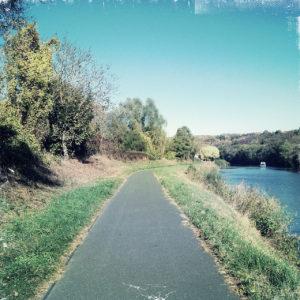 links eines Kanals in einer Flussaue führt ein geteerter Weg.Weit weg ein kleines Hausboot.