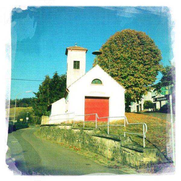 Ein schrill verfärbtes Bild in siebziger-jahre-Farbfilmstil eines einfachen Feuerwehrhauses mit Schlauchturm. Daneben ein Baum mit kugelförmiger Krone. Vermutlich eine Kastanie.