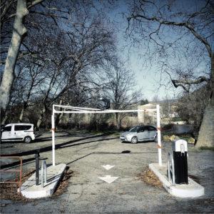 Einfahrt zu einem Parkplatz unter Platanen. Zwei Autos parken. Über der Durchfahrt ist eine Begrenzung gegen Wohnmobile und Wohnwagen in ca. zwei Metern Höhe.