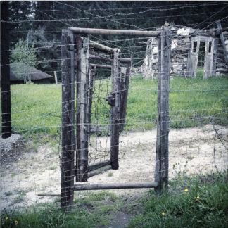 In einem Stacheldrahtverhau befindet sich eine halb offene, holzgerahmte Tür aus verspanntem Stacheldraht.