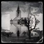 Schwarz-weiß-Bild einer französischen Dorfkirche mit verstümmelter alter Platane als Spiegelung, die wie eine Fatamorgana wirkt. Die Turmuhr zeigt 15:44 Uhr.