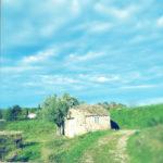 Ein steinerenes, kleines Hüttchen in grünlich-bläulicher Landschaft