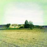 Ein provencalisches Landgut, grün-gelblich fehlfarben unter cyanfarbenem Himmel. Kahles Feld davor.