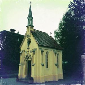 Fehlfarbig fliederfarben vignettiert füllt eine schlanke, winzige, innerstädtische Kapelle das quadratische Bild, düsterlich vor ins Schwarze absaufendem Hintergrund aus Bäumen und Häusersilhouetten.