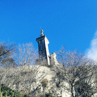 Einen felsigen, von winterlich südfranzösischem Bewuchs gezierten Hang hinauf blicktman auf einen quadratischen Turm, auf dessen Flachsach eine Figur thront. Viel blauer Himmel.