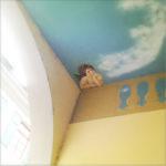 Unter einem Torbogen bei einem Durchgang ein Deckengemälde mit kindlichem Engel, der das speckige Kinn auf den Ellenbogen stützt. Himmel und Wölkchen in Pastellblau und -beige.