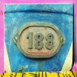 Bunter Rahmen gelb und rosa um eine Zahl 188, die als Alurelieffplatte an einem blauen Hintergrund verschraubt ist.