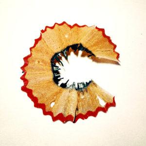 Bleistiftspitzabfall, der aussieht wie ein fett gedrucktes großes C. Der zackige rote Rand umgibt faltige Holzstruktur und innen sind Graphitreste mit kleinen Spitzen. Der Hintergrund ist weiß.