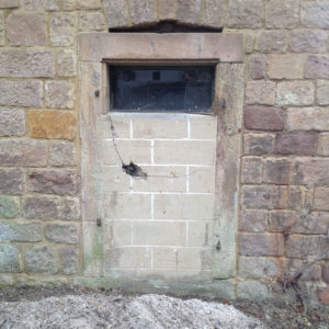 Mit Bimssteinen vermauerte Tür in einer Wand aus beige-rotem Sandstein.