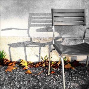 Ein Gartenstuhl wirft einen sanften Schatten nach links an eine Wand. In der Ritze zwischen Wand und Terrassenboden liegt Laub und es keimt etwas kleines Grünes.