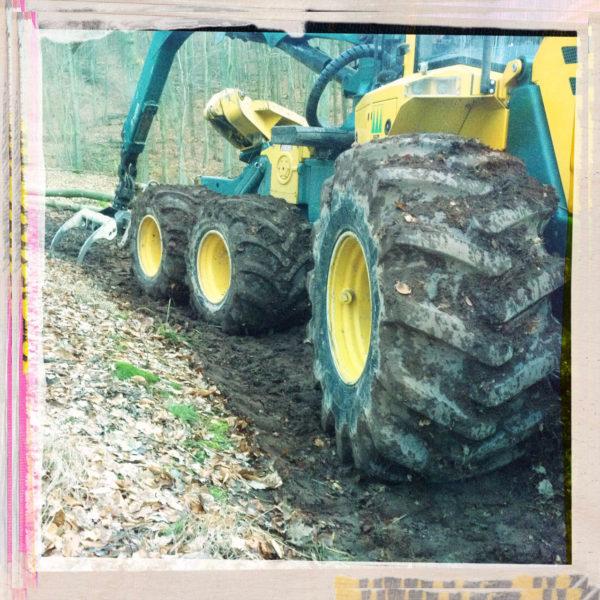 Gelblich-bläuliche Forstmaschine mit drei Rädern und Hundeganglenkung seitlich im Profil ins rosa gerahmte Bild einer winterlichen Rodungsfläche führend.