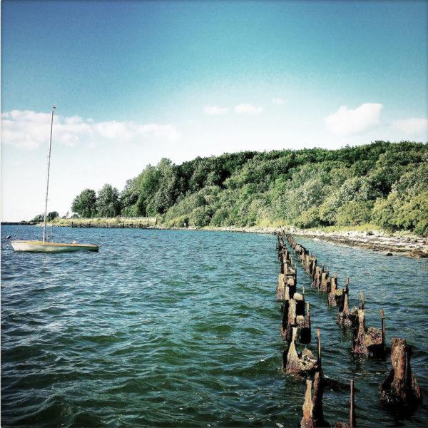Wellenbrecher aus rostigen Stahlstangen führen durchs Meer auf eine grüne Halbinsel zu. Ein Segelboot ankert.