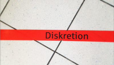 Auf schräge zur waagrechten roten Klebebandlinie verlaufenden weißen fließen steht geschrieben Diskretion. Draufsicht in einem Wartebereich