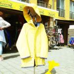 Ein gelber Regenmantel auf einem Kleiderständer vor einer touristischen Verkaufszeile in einer norddeuteschen Stadt.