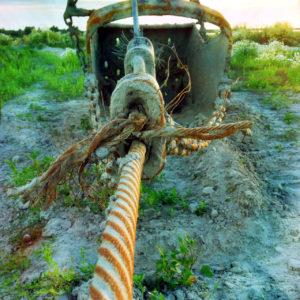 An armdickem, rostigem Stahlsein spannt sich ein Verschluss, der eine dicke Kette anbindet, an der eine Zugbaggerschaufel hängt.