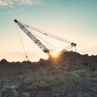 Ein weit auslragender Kran auf einem Sandabbaugelände vor untergehender Sonne